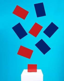 Os cartões azuis e vermelhos do conceito eleitoral caem em uma caixa de votação branca