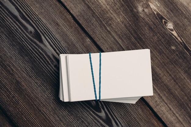 Os cartões de visita em uma mesa de madeira financiam o trabalho de escritório copiar espaço.
