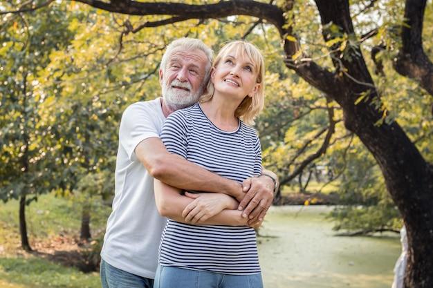 Os casais idosos se abraçam e sorriem alegremente.
