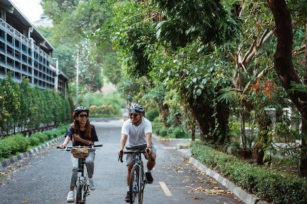 Os casais jovens asiáticos que usam capacetes gostam de andar de bicicleta juntos