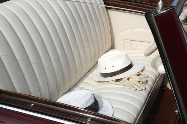 Os chapéus e as luvas antiquados brancos nas cadeiras de carro de couro aparam no automóvel retro.