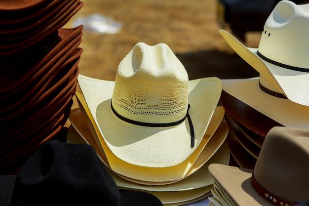 Os chapéus exibem para venda em um mercado de rua.