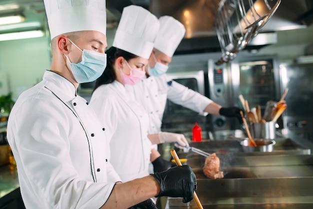 Os chefs em luvas e máscaras protetoras preparam os alimentos na cozinha de um restaurante ou hotel.