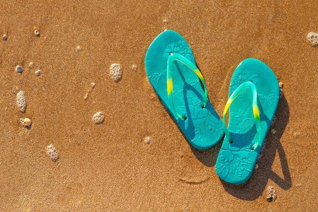 Os chinelos das mulheres estão na praia na areia, conceito das férias