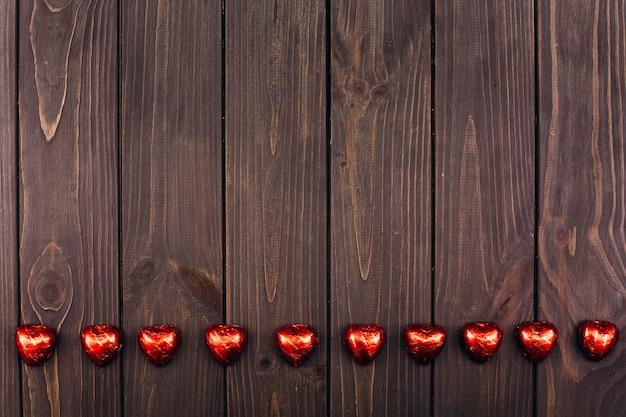 Os chocolates em forma de corações encontram-se na mesa de madeira
