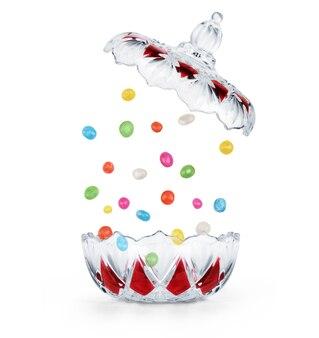 Os chocolates estão caindo na bala transparente em um fundo branco