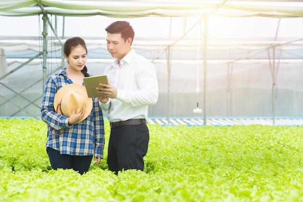 Os cientistas asiáticos dos jovens verificam o controle de qualidade dos alimentos da agricultura e mostram o resultado com o agricultor asiático.