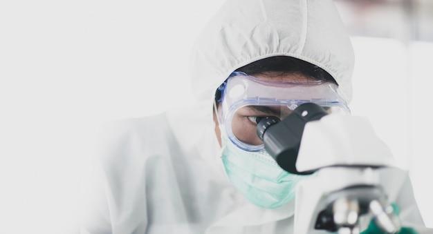 Os cientistas estão olhando para um microscópico para estudar e fazer pesquisas. para produzir vermes terapêuticos, a pesquisa de medicamentos contra o vírus corona
