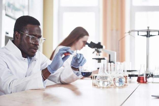Os cientistas trabalham em estreita colaboração com o microscópio no laboratório, conduzindo experimentos e análises.