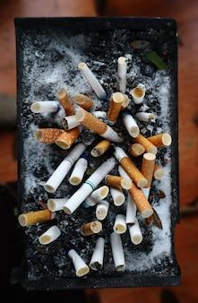Os cigarros são deixados no cinzeiro na área de fumantes
