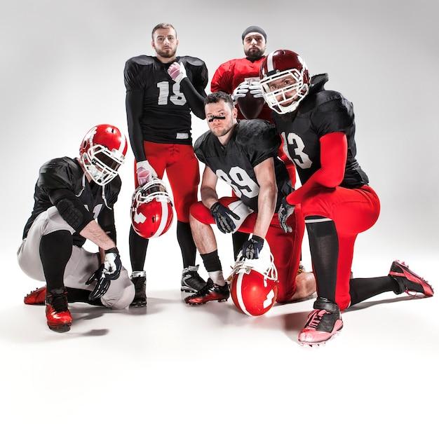 Os cinco homens caucasianos de fitness como jogadores de futebol americano posando de corpo inteiro com uma bola no fundo branco
