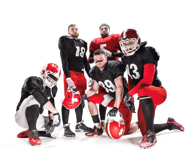 Os cinco jogadores de futebol americano posando com a bola no fundo branco
