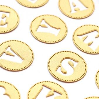 Os círculos do fundo e da textura do papel textured dourado sob a forma das moedas e as letras cortaram deles.