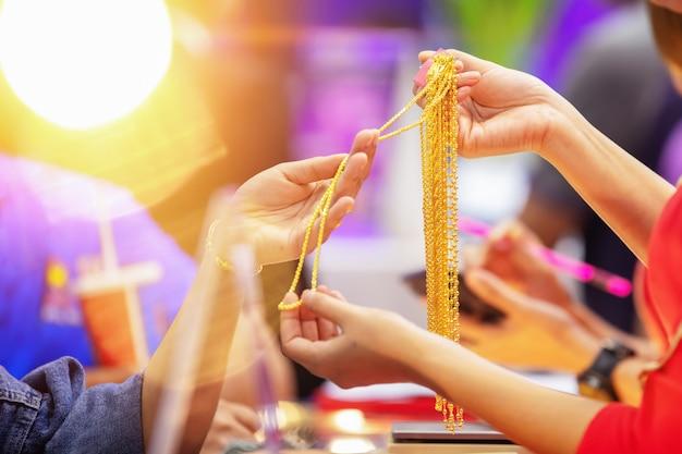 Os clientes estão comprando jóias de ouro na loja de ouro