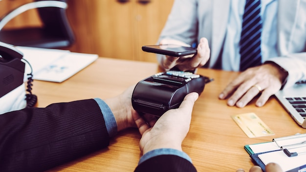 Os clientes que pagam fatura dinheiro rápido financeiro por tecnologia de pos pagamento nfc com aplicativo móvel no smartphone.