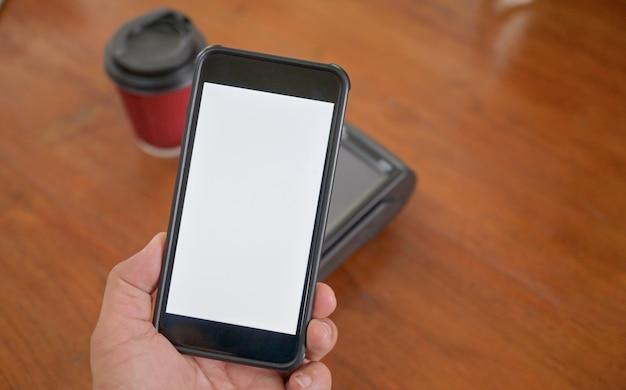 Os clientes usam uma digitalização de smartphone para pagar no terminal de pagamento.