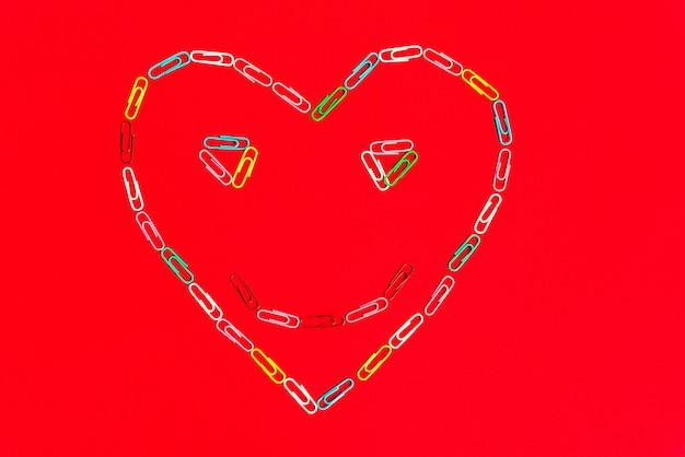 Os clipes de papel coloridos dos artigos de papelaria caoticamente dispersaram e fizeram o coração do sorriso no fundo vermelho.