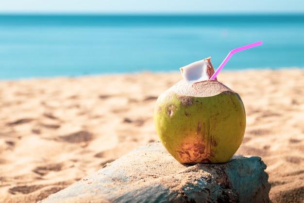 Os cocos verdes doces molham com palha bebendo na praia da areia em phuket tailândia.