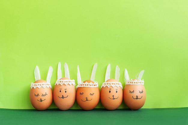 Os coelhos engraçados de easter eggs no fundo do papel verde com espaço da cópia.