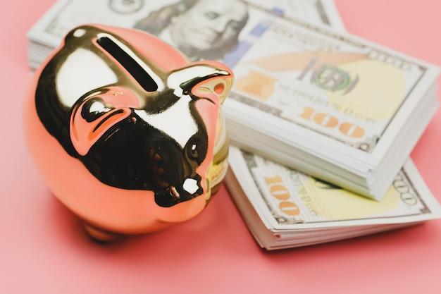 Os cofrinhos do close up e um modelo de casa com notas de dólares americanos para salvar para comprar uma casa na parede rosa. investimento imobiliário e hipoteca da casa financeira.