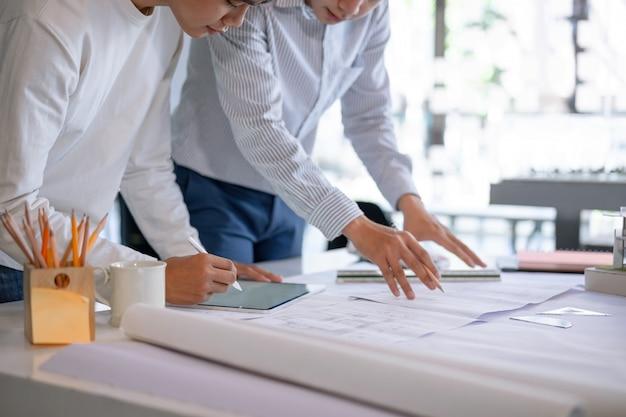 Os colegas asiáticos novos do arquiteto que discutem sobre a construção planeiam no modelo e na tabuleta no escritório do canteiro de obras.
