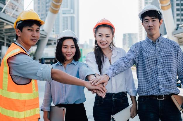 Os colegas de trabalho dos engenheiros se unem para construir projetos de sucesso. conceito de trabalho em equipe.