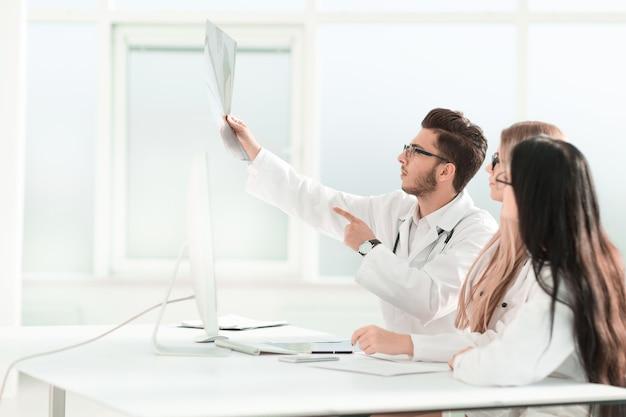 Os colegas médicos discutem a radiografia do paciente .foto com espaço de cópia