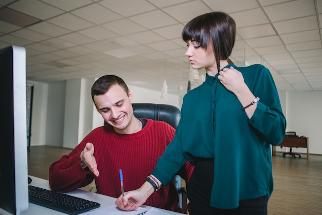 Os colegas positivos do jovem hippie no escritório no computador discutem o trabalho.
