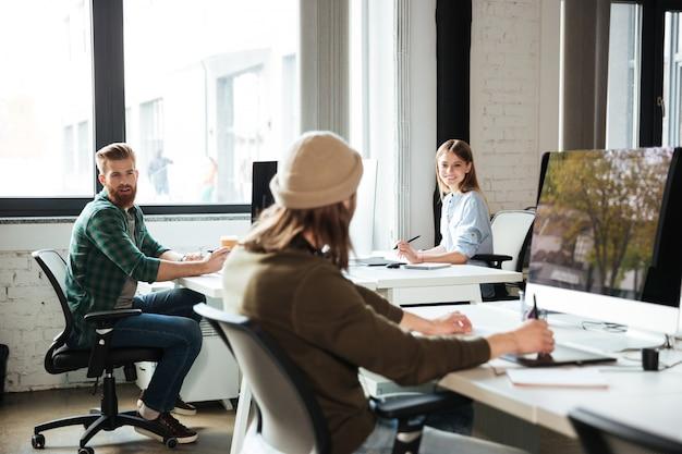 Os colegas trabalham no escritório usando computadores. olhando de lado.