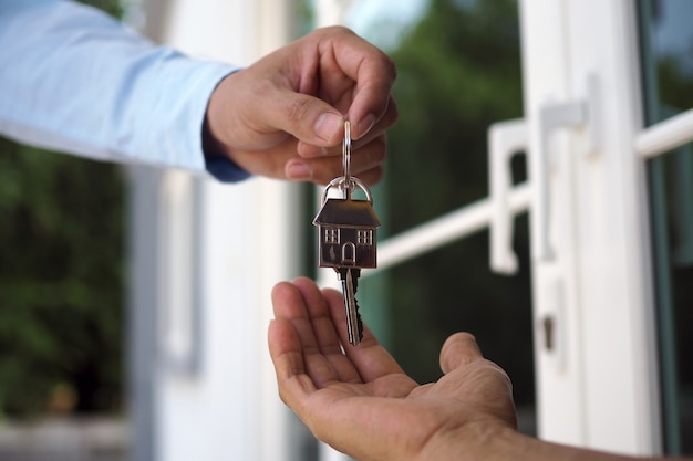 Os compradores home estão levando as chaves para casa dos vendedores. venda a sua casa, alugue uma casa e compre ideias.