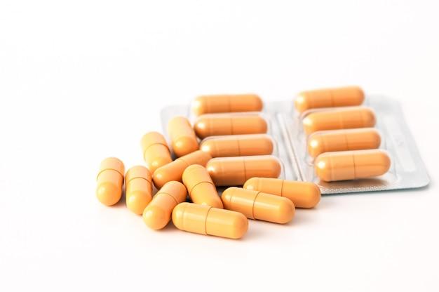 Os comprimidos e as bolhas amarelos brilhantes dispersaram em um fundo branco. isolado.