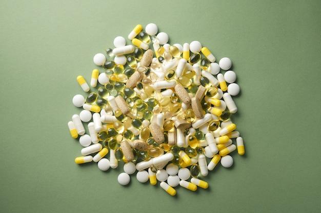 Os comprimidos estão espalhados sobre a mesa. comprimidos no fundo verde. comprimidos medicinais, cápsulas.