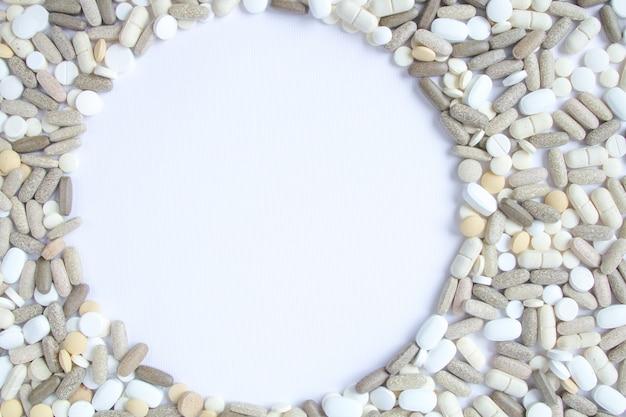 Os comprimidos médicos coloridos afrouxam em um fundo branco.