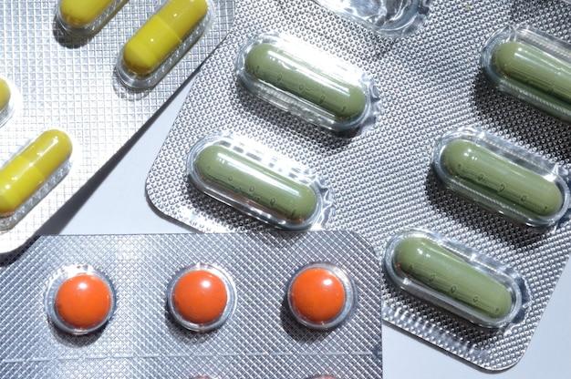 Os comprimidos multicoloridos em bolhas de alumínio ficam sobre um fundo claro. fechar-se.