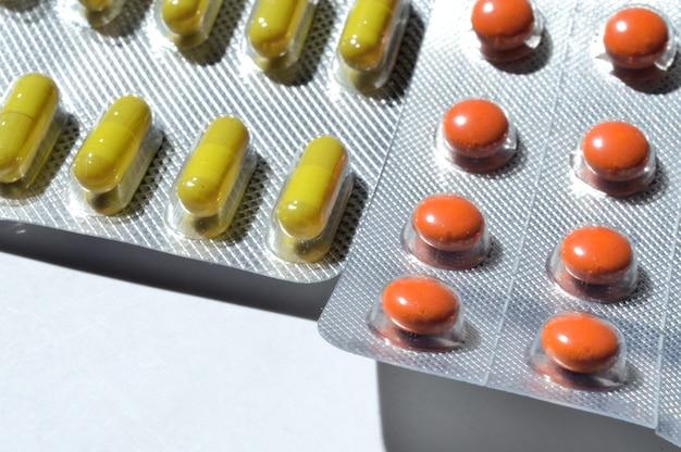 Os comprimidos são embalados em bolhas, sobre um fundo claro. fechar-se.