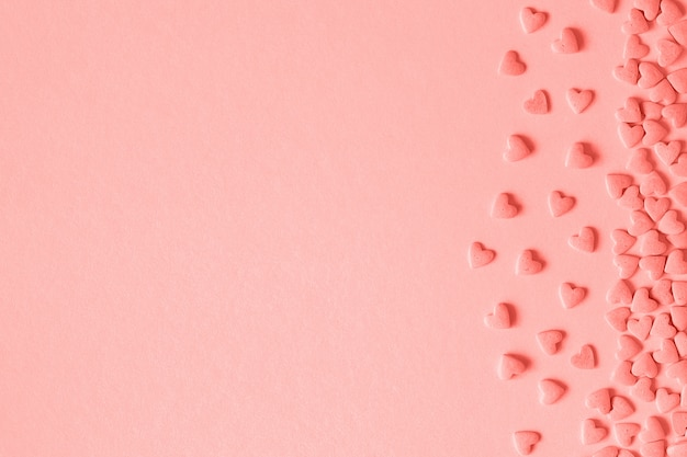 Os confeitos dos corações polvilham situado no lado direito no fundo cor-de-rosa no coral tonificado.