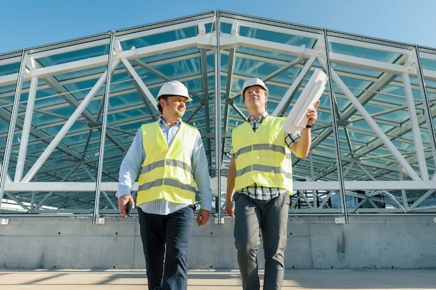 Os construtores masculinos vão para a frente no telhado do canteiro de obras.