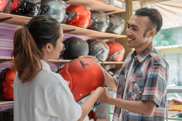 Os consumidores do sexo masculino sorriem ao escolher um capacete servido por uma bela lojista em uma loja de capacetes