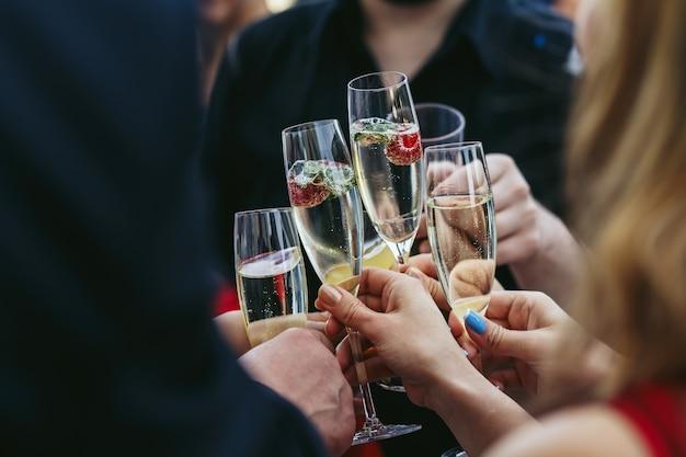Os convidados clang óculos de champanhe com deliciosos morangos