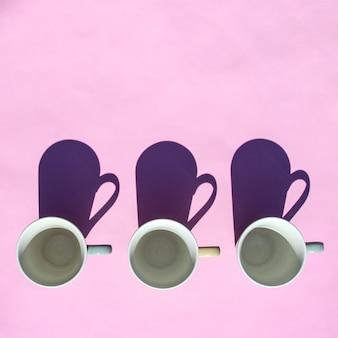 Os copos vazios do café e de chá estão na fileira na tabela na luz solar com sombras.