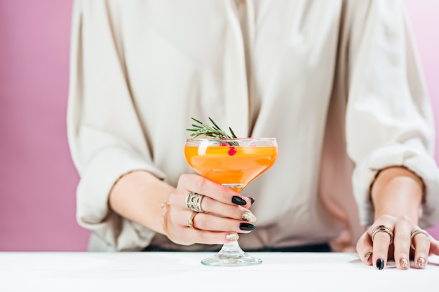 Os coquetéis exóticos rosas e frutas e mão feminina