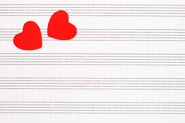 Os corações do papel vermelho encontram-se em um caderno de música limpo.