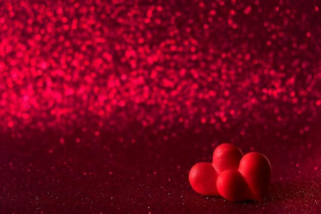 Os corações vermelhos brilhantes abstraem fundo vermelho bokeh. textura de dia dos namorados.