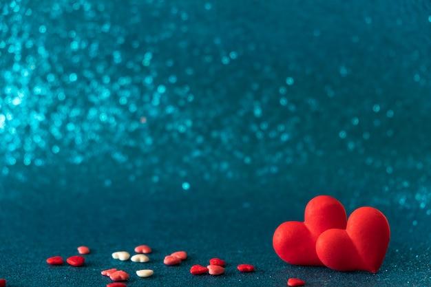 Os corações vermelhos brilhantes abstraem o fundo azul do bokeh. textura de dia dos namorados.