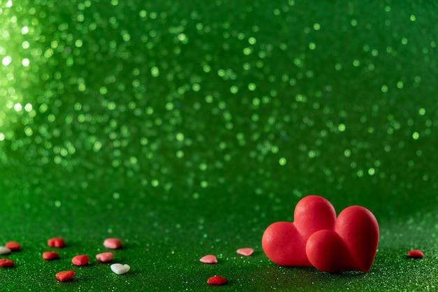 Os corações vermelhos brilhantes abstraem o fundo verde do bokeh. textura de dia dos namorados.