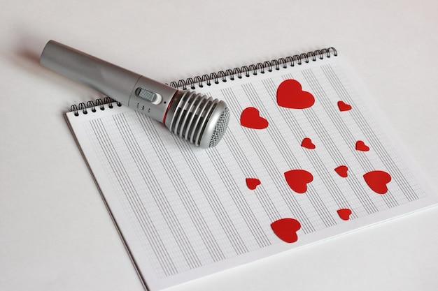 Os corações vermelhos de microfone e papel estão localizados em um bloco de notas de música limpo.