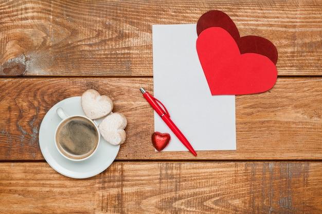 Os corações vermelhos e uma folha de papel em branco e uma caneta em um fundo de madeira com uma xícara de café