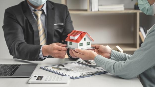 Os corretores de imóveis oferecem designs de casas para os clientes negociarem com um contrato de empréstimo hipotecário no escritório.