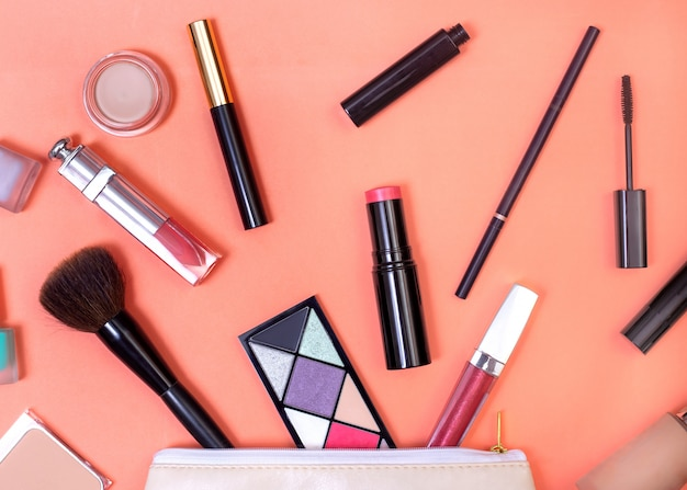 Os cosméticos caíram da bolsa de cosméticos em um fundo de coral