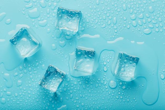 Os cubos de gelo com gotas da água espalharam em um fundo azul, vista superior.